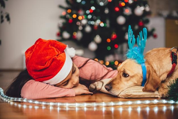 Menina e cachorro deitado junto à árvore de natal Foto Premium