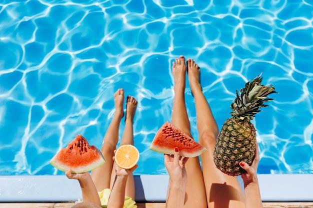 Menina e criança sentada à beira da piscina com frutas tropicais nas mãos Foto Premium