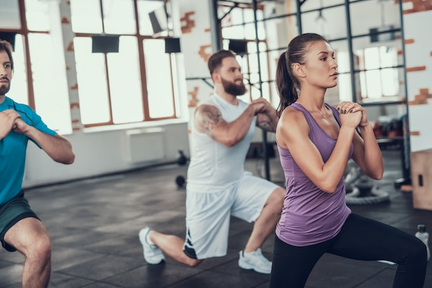 Menina e dois caras que fazem lunge exercícios no ginásio. Foto Premium