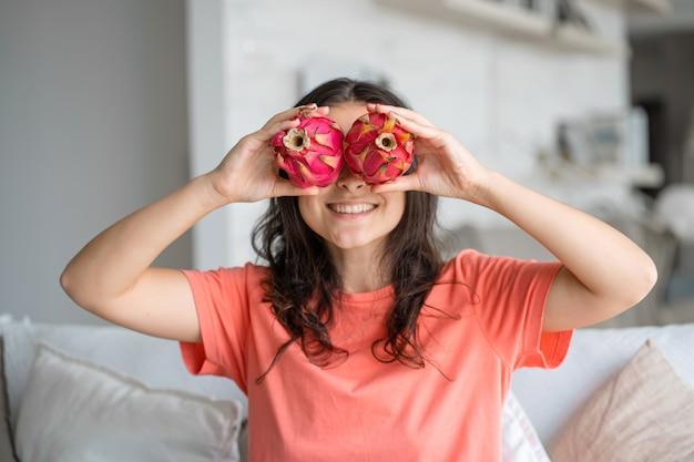 Menina e fruta do dragão. menina alegre, desfrutando de frutas tropicais. Foto Premium