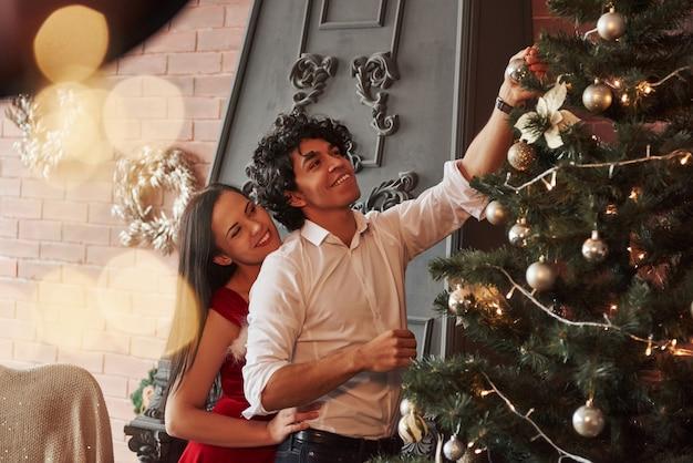 Menina e homem estão sorrindo durante o processo. par romântico de vestir a árvore de natal na sala com parede marrom e lareira Foto Premium