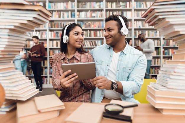 Menina e indivíduo indianos cercados por livros na biblioteca. Foto Premium