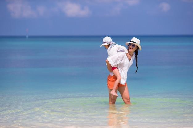 Menina e jovem mãe durante as férias de praia Foto Premium