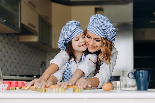 Menina e mãe estenda a massa com um rolo juntos. Foto Premium