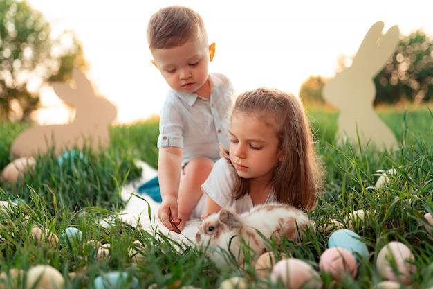 Menina e menino brincam com o coelho rodeado de ovos de páscoa Foto Premium