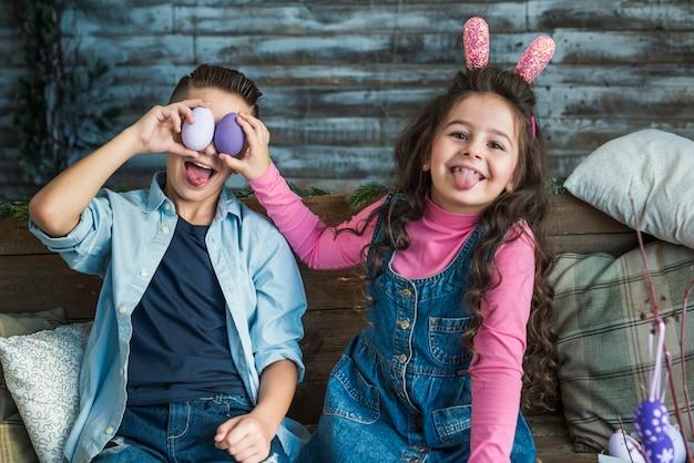 Menina e menino com ovos de páscoa fazendo caretas Foto gratuita