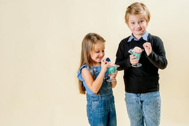 Menina e menino comem sorvete em uma luz de fundo Foto Premium