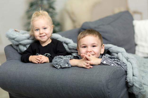 Menina e menino deitado t no sofá coberto com um cobertor de malha cinza e sorrindo Foto Premium