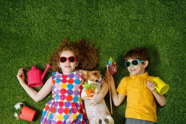Menina e menino e seu cão deitado na grama verde. Foto Premium