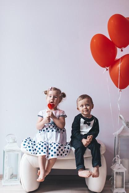 Menina e menino sentado em uma cadeira branca perto de balões em forma de coração. Foto Premium