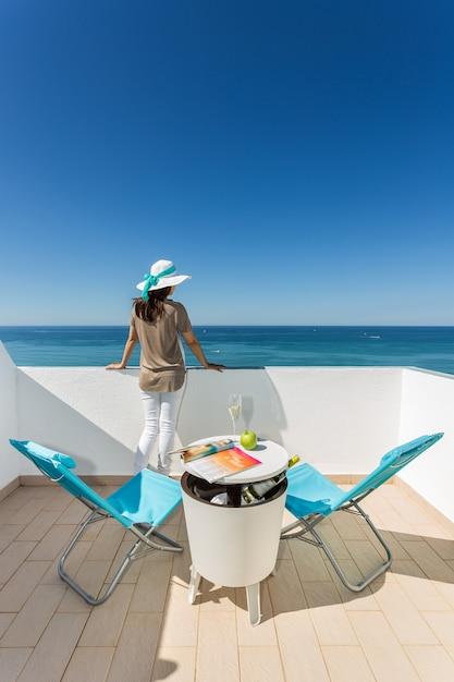 Menina é relaxante no terraço. com uma taça de champanhe com vista para o mar. Foto Premium