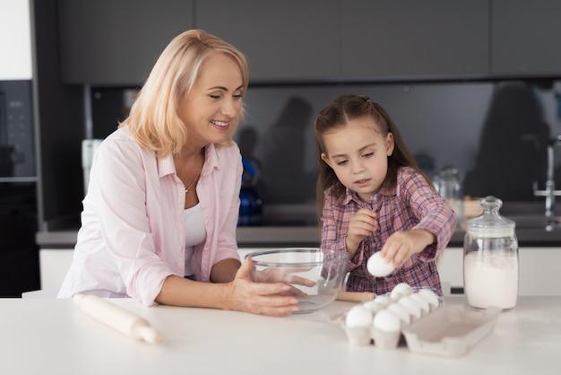 Menina e sua avó na cozinha e preparar bolos. Foto Premium