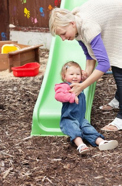 Menina e sua mãe loira se divertindo com uma calha Foto Premium