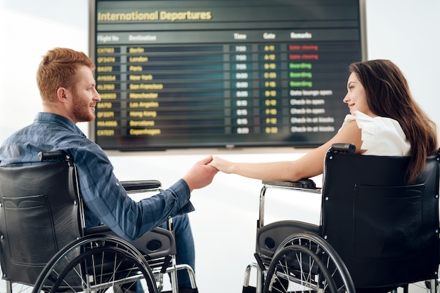 Menina e um cara em cadeiras de rodas perto do horário dos voos. Foto Premium