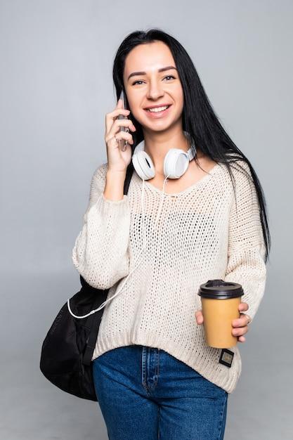 Menina elegante atraente rindo alegremente enquanto fala no telefone celular com o namorado, isolado na parede cinza. conceito de conversa. Foto gratuita