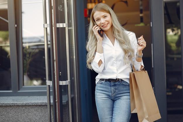 Menina elegante com sacola de compras em uma cidade Foto gratuita