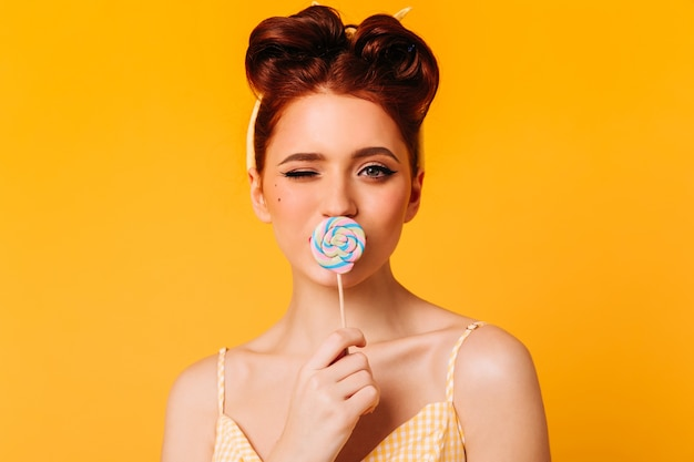 Menina elegante de gengibre lambendo o pirulito. vista frontal da mulher entusiasmada com rebuçados. Foto gratuita