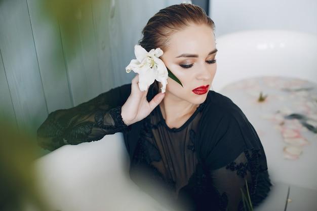 Menina elegante e bonita encontra-se no banheiro Foto gratuita