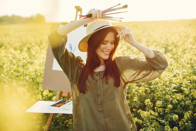 Menina elegante e bonita pintura em um campo Foto gratuita