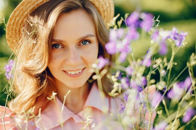Menina elegante e elegante em um campo de verão Foto gratuita