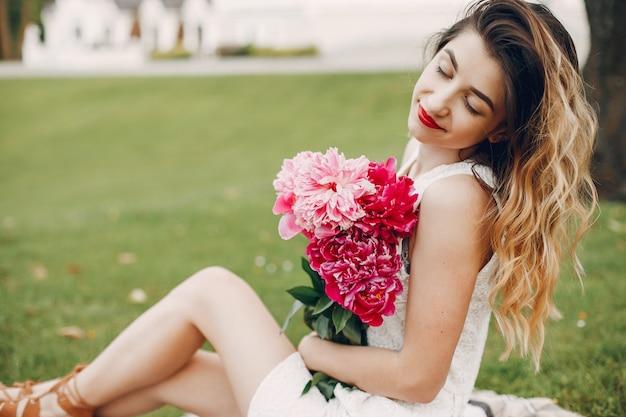 Menina elegante e elegante em um jardim de verão Foto gratuita