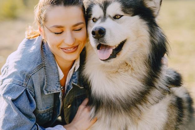 Menina elegante em um campo ensolarado com um cachorro Foto gratuita