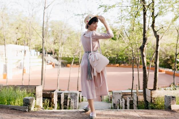 Menina elegante em um traje antiquado olhando por cima do ombro e segurando um chapéu de palha com um sorriso fofo Foto gratuita