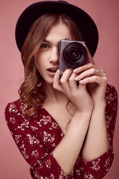 Menina elegante hipster em vestido vermelho, chapéu preto e óculos com câmera Foto Premium