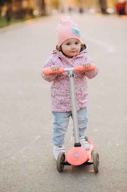 Menina elegante monta uma scooter no parque ao pôr do sol Foto Premium