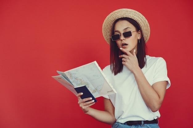 Menina elegante posando com equipamento de viagem em uma parede vermelha Foto gratuita