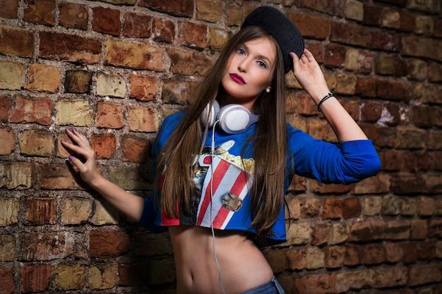 Menina elegante posando perto de uma parede de tijolos Foto gratuita