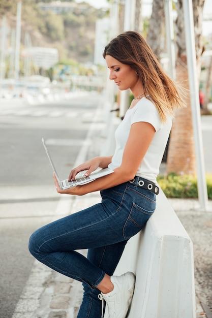 Menina elegante segurando um laptop ao ar livre Foto gratuita