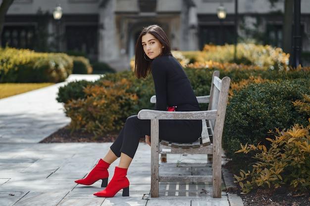 Menina elegante, sentado em um banco na escola Foto gratuita