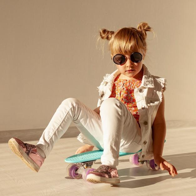 Menina elegante, sentado no skate Foto gratuita
