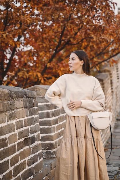 Menina elegante, visitando a grande muralha da china, perto de pequim durante o outono Foto gratuita