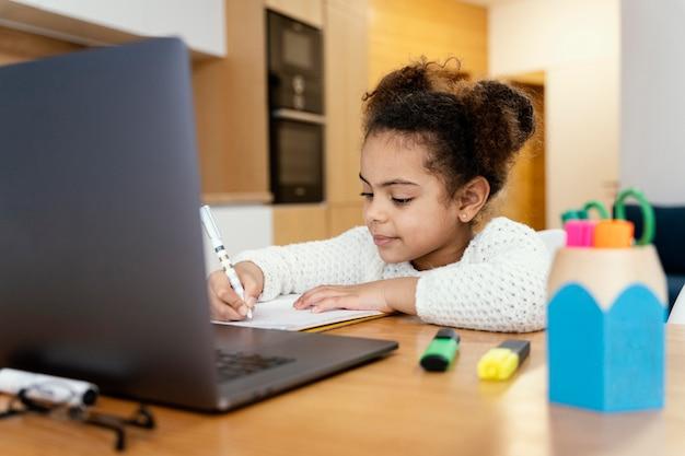 Menina em casa estudando durante a escola online com laptop Foto gratuita