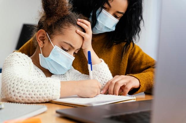 Menina em casa usando máscara médica durante a escola online com a irmã mais velha Foto gratuita