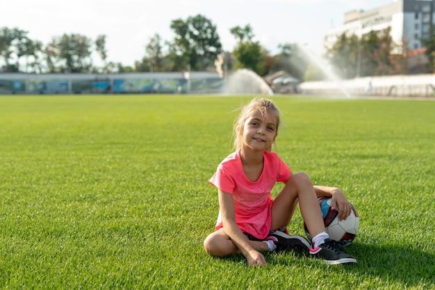 Menina, em, cor-de-rosa, t-shirt, sentando, ligado, campo futebol Foto gratuita