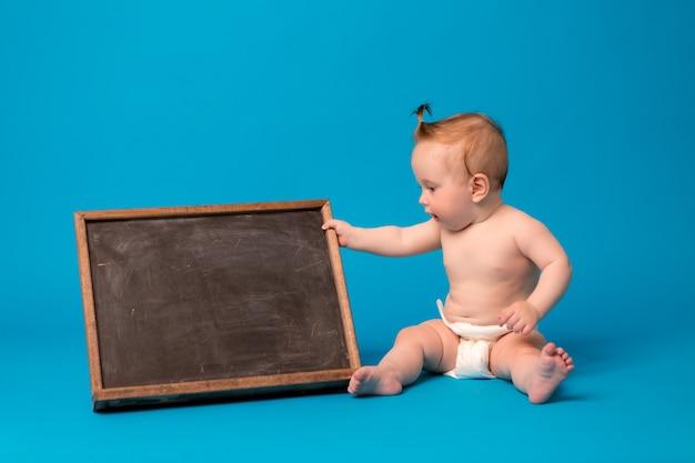 Menina em fraldas, segurando uma prancheta de desenho sobre um fundo azul Foto Premium