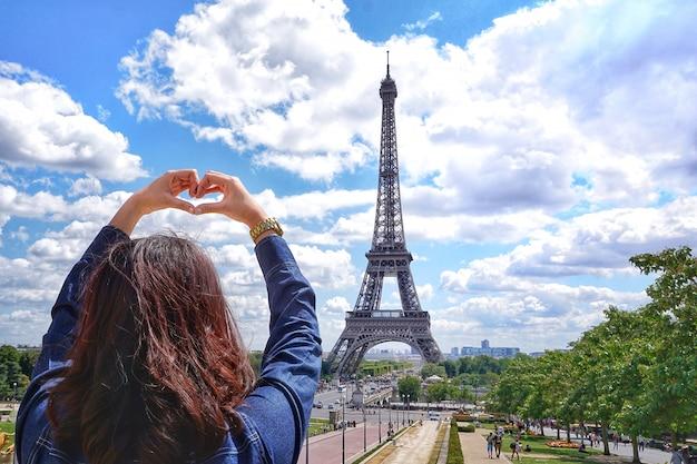 Menina, em, mão, sinal coração, com, camisa brim, em, férias verão, ligado, céu, e, torre eiffel, em, fundo, em, paris Foto Premium