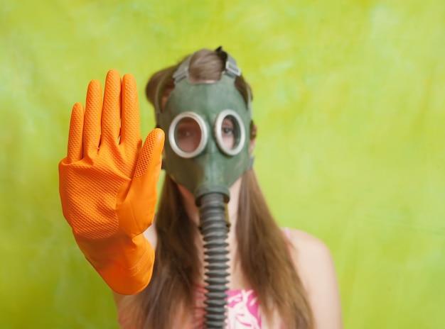 Menina em máscara de gás apontando stop Foto gratuita