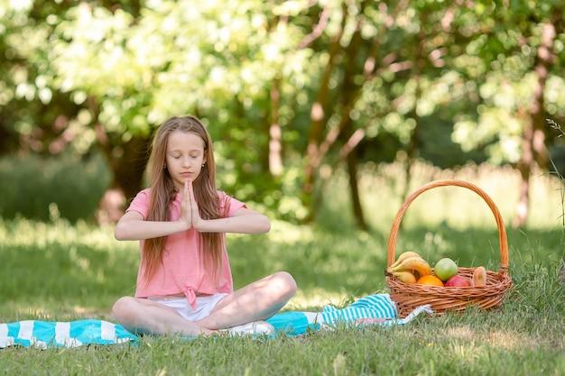 Menina em posição de ioga no parque, Foto Premium