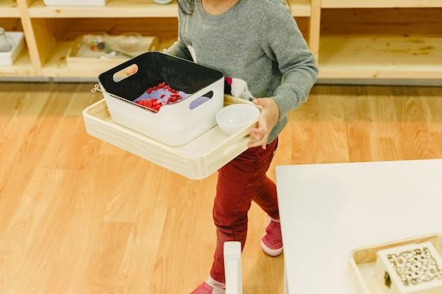 Menina em sua escola montessori movendo bandejas com material Foto Premium