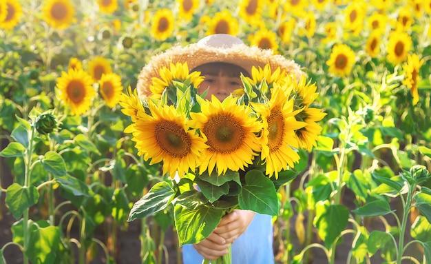 Menina em um campo de girassóis florescendo Foto Premium
