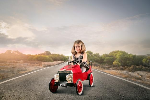 Menina em um carro de brinquedo Foto Premium