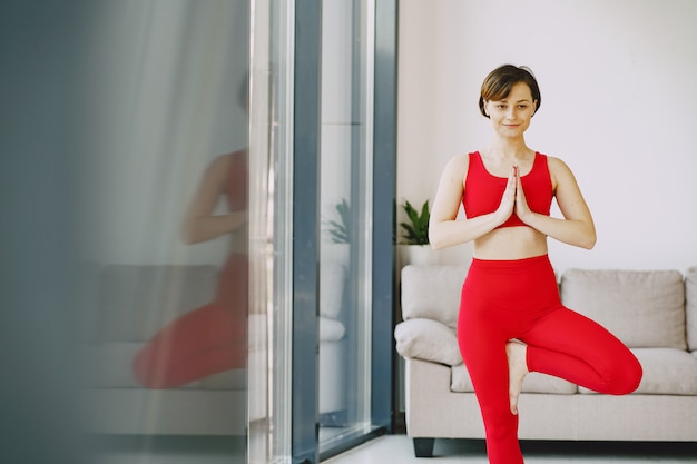 Menina em um uniforme vermelho esportes praticando ioga em casa Foto gratuita