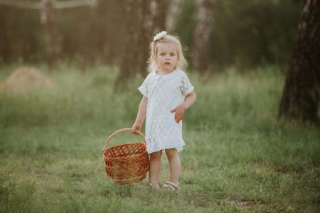 Menina em um vestido branco com uma cesta no parque. linda menina andando em um jardim ensolarado com uma cesta Foto Premium