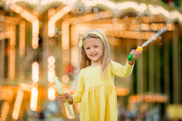 Menina em uma caminhada em um parque de diversões com bolhas de sabão Foto Premium