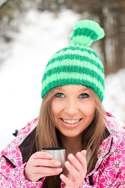 Menina em uma jaqueta carmesim e chapéu verde bebendo chá quente de um termo em montanhas nevadas Foto gratuita