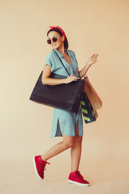 Menina em uma parede amarela com sacolas de compras Foto gratuita